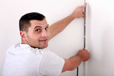 Man fixing wire to wall photo