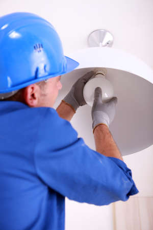 Electrician fitting a ceiling light photo