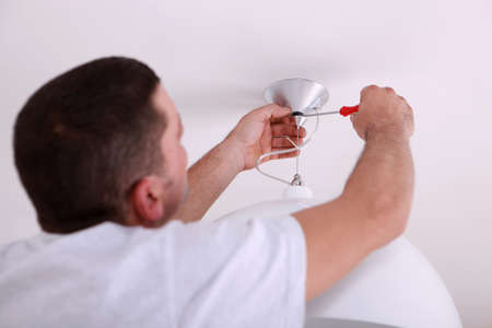 Man repairing ceiling light with screwdriver photo