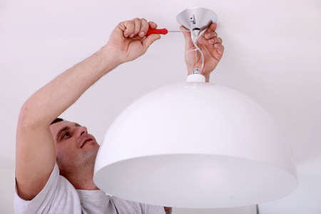 t bulb: Man fixing ceiling light