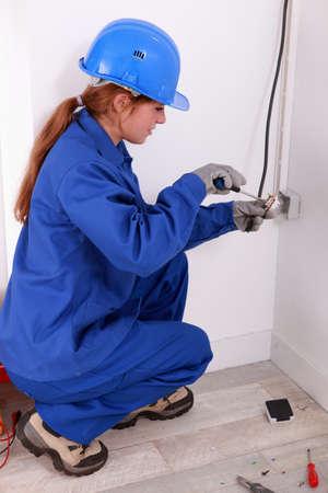 wall socket: Female electrician installing a wall socket
