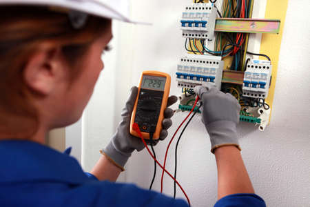 fusebox: Female electrician checking a fusebox Stock Photo