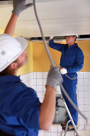 feeding through: Two electrician feeding length of cable through ceiling