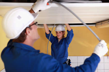 Two electricians working on the ceiling Stock Photo - 11774761
