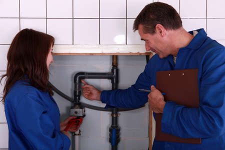 jumpsuit: a mature plumber teaching to a female apprentice