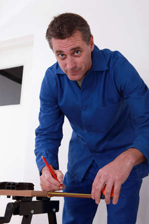 45 years old: carpenter using a steel measuring tape for drawing a mark on a board