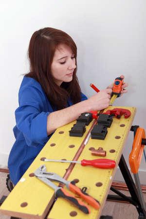 koperen leiding: Vrouw loodgieter meten koperen buis Stockfoto
