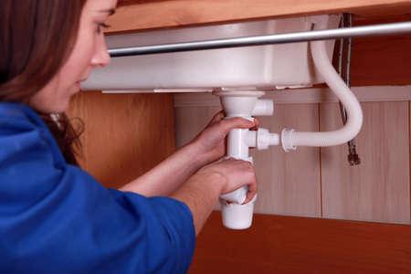 drenaggio: Donna che fissa l'impianto idraulico su un dissipatore Archivio Fotografico