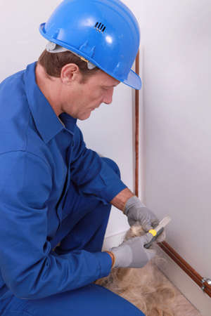 hunker: plumber working indoors