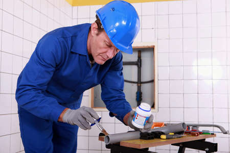 plumbing supply: Plumber applying glue to a grey plastic pipe Stock Photo