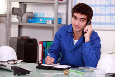 writing materials: factory worker talking on the phone Stock Photo