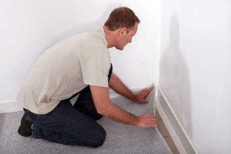 Man installing carpet in room photo