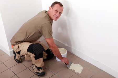 adherent: Man spreading adhesive over old floor tiles