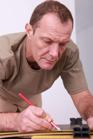 45 49 years: Man measuring and marking wood Stock Photo