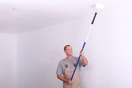 long handled: Man painting a room white