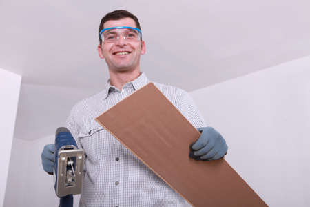 Man preparing to cut wood with a jigsaw photo