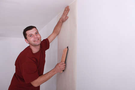 Decorator smoothing down wallpaper with a brush photo