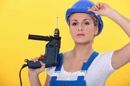 take it easy: a blonde woman wearing an overall posing with a drill and adjusting her helmet Stock Photo
