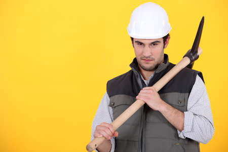 craftsman holding pickaxe against yellow background photo