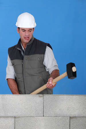 destroying: picture of bricklayer destroying wall with hammer