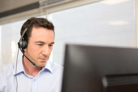 voip: Man using a headset at a computer Stock Photo