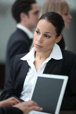 Female executive working with colleague at a laptop photo