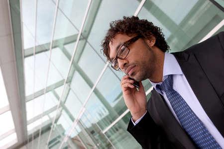 Businessman outside office making phone cal photo