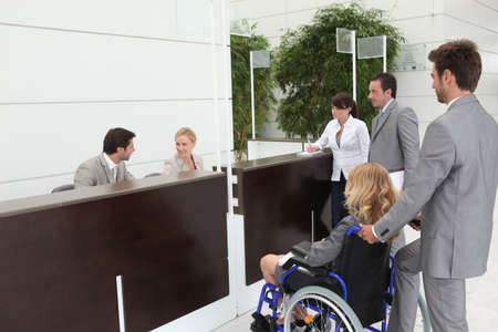 wheelchair access: Businesswoman in a wheelchair with her colleagues at reception