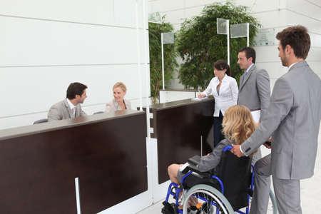 personas discapacitadas: De negocios en una silla de ruedas con sus colegas en la recepción