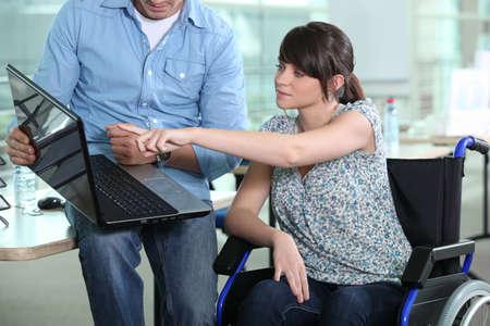 discapacidad: Mujer joven en silla de ruedas mirando la computadora portátil Foto de archivo