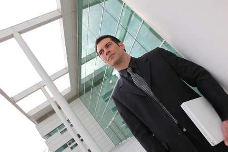 Businessman carrying a laptop photo
