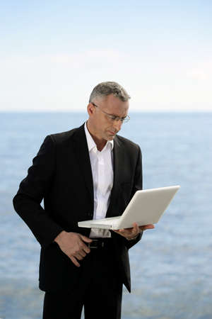 Businessman with laptop stood by lake photo