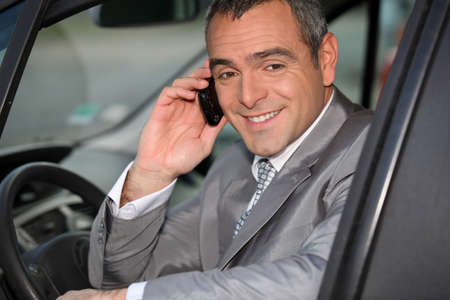 Businessman using a cellphone in his car photo