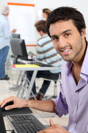 computer lesson: Young man sitting in classroom Stock Photo