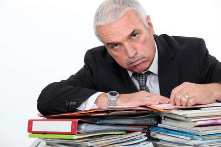 exasperate: Man leaning on paperwork Stock Photo