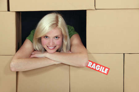 assertive: Woman surrounded by a wall of packing boxes