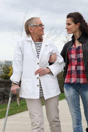 ancianos caminando: Mujer joven ayudando a los ancianos a caminar con una muleta