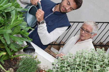 aide � la personne: jeunes arrosage des plantes de l'homme avec femme plus �g�e Banque d'images