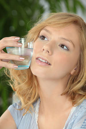affected: young blonde with glass of water against cheek Stock Photo
