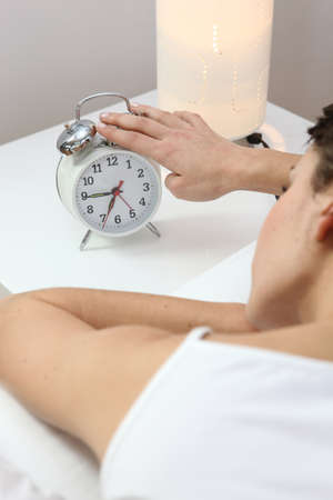 Woman tapping an alarm clock photo
