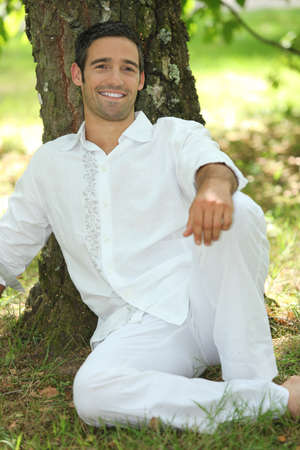 take it easy: Man in white relaxing against a tree Stock Photo