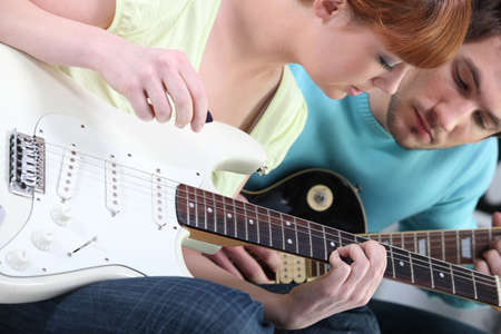 Girl learning to play guitar photo