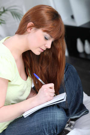 Young woman writing in a notebook photo