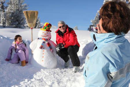 abuelos: La abuela de tomar una foto de su familia y su mu�eco de nieve Foto de archivo