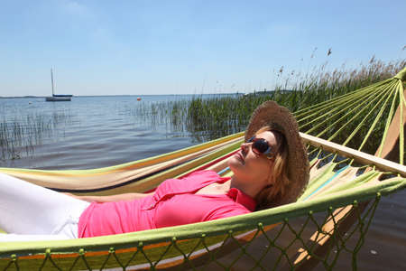Woman in straw hat relaxing on a hammcock photo