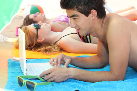 Young man at the beach with his laptop Stock Photo - 11775355