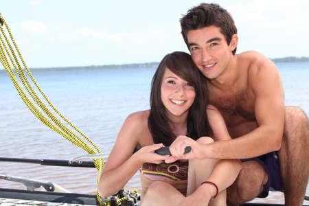 skipper: Young couple steering a catamaran