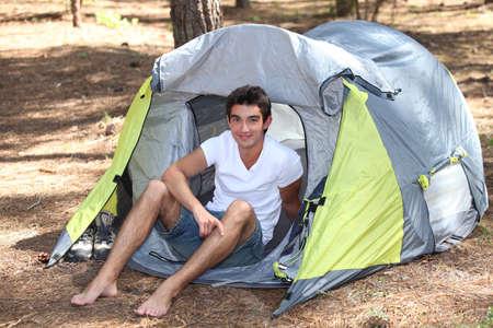 Teenage boy sat in tent photo
