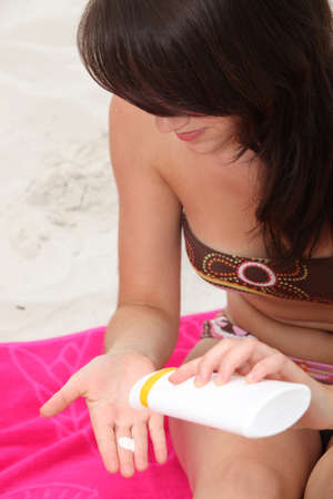 brunette at beach applying suncream photo