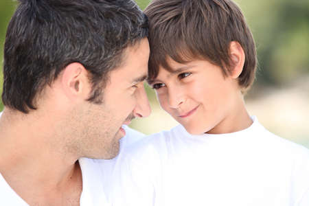 a father and his son looking each other in the eyes photo